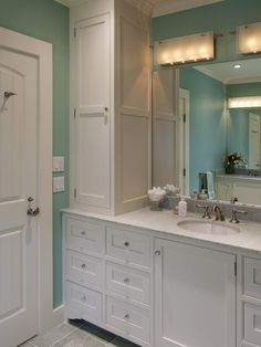 A tall cabinet utilizes formerly wasted space and makes toiletries and grooming tools easily accessible yet out of sight in this blue bathroom. Designer Tip: Designer Elizabeth Swartz says keep scale in mind when adding this type of storage unit to a bathroom to avoid overpowering the space.