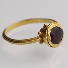 Byzantine Cup Bezel Ring: NO RESERVE (500 - 700) Flat band with a strip of beaded wire forming a ridge, joining at the shoulders a cup bezel with six globules at the base, decorated with beaded wire and set with a garnet cabochon.