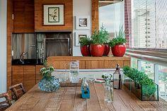 Cozinha gourmet | Toda a marcenaria, que inclui os painéis, o gabinete, a bancada e a mesa, tem desenho da arquiteta e execução da Projeart. Garrafas da Kare e vasos da Saccaro. Persianas da Arthur Decor