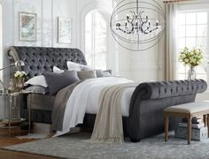 From the Bombay Collection. Romantic detailing meets exaggerated sleigh bed style. Brings a touch of class to any bedroom. Available in gunmetal and linen beige fabrics.