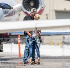 Lip lock: Blake and Gwen embraced and kissed on the tarmac in front of the jet plane they'...