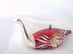 This vintage Christmas ornament was made in a blow mold. The silver and red double indent bird ornament has a white spun glass tail and white