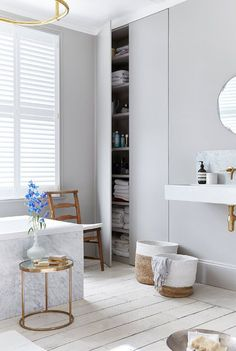 A contemporary, luxurious bathroom look with a simple grey colour scheme,  limewashed floor boards and statement shutters