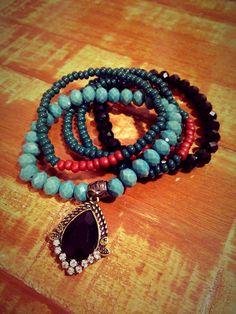 Mix de pulseiras contendo 5 pulseiras, sendo 3 em miçangas verdes e coral, 1 em contas de cristal trabalhado preto e 1 em contas de cristal verde com um berloque bronze com cristal negro e mini strass