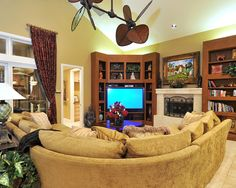 Curved sectional sofa in tropical family room design with fireplace mantle and creative bookshelves plus corner tv cabinet also recessed lighting and Living Room Corner Decor, Living Room Tv, Media Room Design, Family Room Design, Corner Entertainment Unit, Corner Tv Cabinets, Small Media Rooms, Living Room Sectional, Sectional Sofa