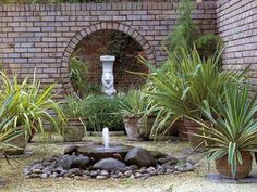 The stone water fountain with the lion statue background and the brick walls blend to make the place mystical.
