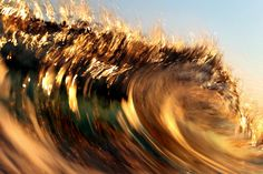 Breaking waves reflect golden light from a sunset at Wrightsville Beach, N.C.The motion effect is from moving a camera (panning) along the same motion the wave is moving while using a slow shutter speed.