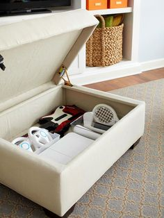 Use an ottoman to organize video game controllers and keep your living space organized. Love!