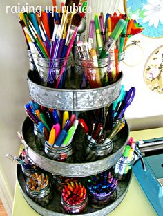 Love this idea for kids art supplies... used jars and open containers and then old three tiered tin thingy to hold them all together. You could put it a turn about on bottom to usability.