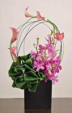 calas rosas mini, mattiola, y drácena en una base obscura para generar un contraste.