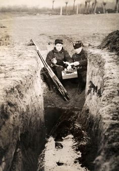 Two Belgian soldiers having a Christmas meal in a dry corner of a flooded trench on the Western Front, December 1915