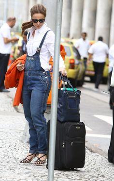 Paolla Oliveira ao desembarcar no aeroporto Santos Dumont, no Rio, vestindo uma jardineira - macacão jeans, salto alto e casaco laranja