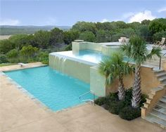 Three tiered Mediterranean style pool with natural stone coping and colored concrete decking.