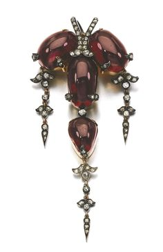 GARNET AND DIAMOND BROOCH/PENDANT, 1870S. Set with carbuncle garnets, suspending cushion-shaped and rose diamonds pampilles.