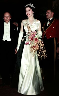 1952 from Queen Elizabeth II's Royal Style Through the Years Queen Elizabeth attended a Royal film performance at Leicester Square in London wearing a two-tone gown and matching gloves.