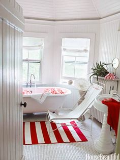 A striped rug from Ikea brightens the bath in a Bridgehampton, New York house's bathroom.