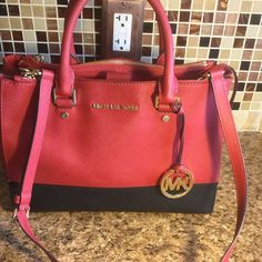 """MK Sutton Handbag /Make Offer In good condition/ except slight rip to side of bag seen in pics/ barely visible/ pen marks inside bag bought for $328.Medium Color-Block Satchel RED/BLACK  100% Authentic Guaranteed! Double handles with 4.5"""" drop length Adjustable shoulder strap with 18-20"""" drop length Interior features 3 zippered pockets, 3 open pockets, 1 cell phone pocket  Protective feet Dimensions: Bottom Width 12"""" x Height 9"""" x Depth 5""""  Strap Drop Length: 4.5""""  Material: Saffiano Leather…"""