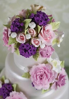 Tarta de boda cubierta con fondant perlado blanco y bouquets de lilas, rosas y peonías realizadas en azúcar.