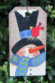 Use this beautiful snowman wood piece as an ornament on your Christmas tree or as a gift tag! There is wire attached for hanging and it is finished with a matte sealer. Measures 2 1 4 W X 4 1 4 H. Designed by Renee Mullins. This item is hand painted wi Wood Snowman, Snowman Crafts, Painted Snowman, Christmas Crafts, Christmas Decorations, Snowman Wreath, Primitive Snowmen, Christmas Wood, Christmas Signs