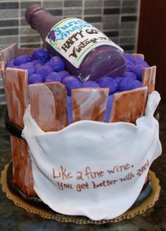 Wine bottle inside a wooden grape basket birthday cake with message that says Like a fine wine, you get better with age.JPG