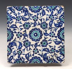 AN IZNIK SQUARE POTTERY TILE with blue and turquoise flower decoration, 20.5cm  Sold for £320