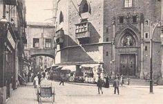 Santa María del Mar. Puerta del Passeig del Born. 1915. Se puede ver:  - El puente que comunicaba el Palacio Real con el coro alto de la iglesia.  - Las tiendas pegadas a la fachada de la iglesia