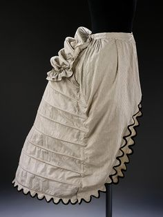 By 1865 the outline of the fashionable dress changed. The shape at the back of the body grew more exaggerated with a distinctive flattening at the front. Crinolettes, or half-crinolines, marked the mid-point between the cage crinoline and the bustle. They often had extra loops of steel, which acted as a bustle.