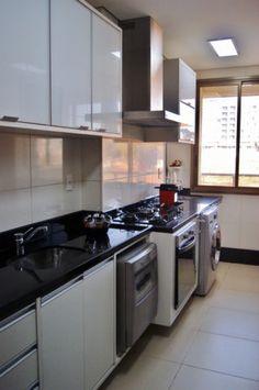 Colocar pia, lava-louças, fogão e lavadora de roupas na mesma parede dá sim. Como prova esta cozinha assinada por Priscila Fernandes. A bancada preta integra todos os eletrodomésticos.