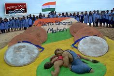 """International sand artist Sudarsan Pattnaik created a sand sculpture to congratulate the Indian Olympic medal winners by creating a 10ft wide sand sculpture of Six Olympic medals with message """"India's Pride"""" and the National flag at the top with a message """"Mera Bharat Mahan"""" at Puri beach of Odisha. Pattnaik also created a sculpture of kusti because in kusti India's Sushil Kumar created the history."""