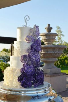 Bestie's Purple Ombre flower Wedding cake. Pearl accents with an cream colored buttercream frosting. Hand made flowers- ombre purple colors. Vineyard Wedding! Great Picture- Masterpiece in person!