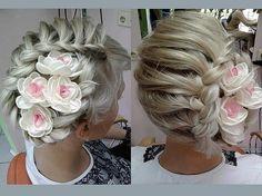 Cette mariée sera certainement ravissante lorsqu'elle se présentera devant son futur époux. Ses longs cheveux blond-blanc ont été ramenés sur un côté de sa tête et le coiffeur y a réalisé une grosse tresse, qui forme un cercle et à l'intérieur duquel il a positionné de jolies fleurs blanc et rose.