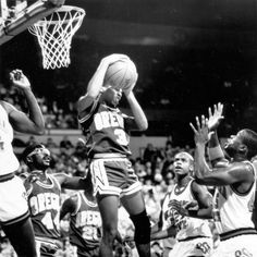 Black and white photo of University of Oregon basketball player Frank Johnson (#3) coming down with a rebound against Oklahoma State during a game played at Memorial Coliseum in Portland on December 27, 1987 and won by the Ducks 68-55. Visible at left are Ducks Brett Coffey (#44) and Anthony Taylor (#21). ©University of Oregon Libraries - Special Collections and University Archives