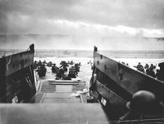 """Landing on the coast of France under heavy Nazi machine gun fire are these American soldiers, shown just as they left the ramp of a Coast Guard landing boat."" Photograph by Robert F. Sargent, June 6, 1944."