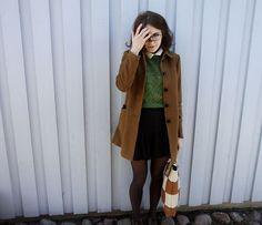 Green sweater. Black skirt.  Tan coat. White collar. Black tights