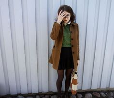 Green sweater. Black skirt.  Tan coat. White collar. Black tights