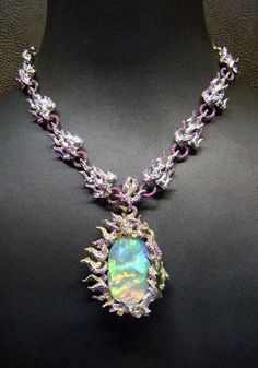 Lot 1610 – A MULTI-GEM 'LIFE IS BUT A DREAM' NECKLACE, BY WALLACE CHAN  Estimate:  $232,925 – $362,328 The necklace suspending a black opal pendant designed as the mythological sun god with circular-cut pink sapphire, yellow sapphire and ruby and vari-cut yellow diamond flames, extending to the similarly designed neckchain, mounted in titanium, 46.0 cm long, in red and black leather Wallace Chan case