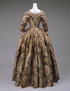 Dress Date: ca. 1725 Culture: British Medium: silk..A Spitalfields silk dress with a dome-shaped skirt conforms not only to the silhouette of the 1730s but also to the interaction between silks and laces during that time, especially evident in Spitalfields manufacture. The silk pattern is like that of lace. While such interaction seems hard to imagine between worker and pattern book, clothing is a place where the various media