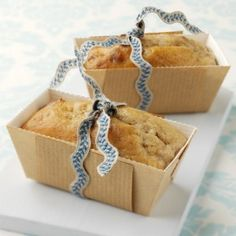 Two banana bread in brown loaf cases tied with blue ribbon