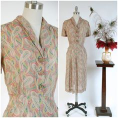 Vintage 1940s day dress is a lovely lightweight number for summery days. Its a smart day dress style, with short sleeves, a shirt waist bodice and skirt with pockets! This classic circa-1940s silhouette features a top stitched collar and a darted gored skirt. The ultra-sheer cotton voile is printed with a very detailed paisley in orange-red, yellow, royal blue and grass green. It closes with a zipper up the side. This will be perfection for the hottest days! ✂-----Measurements  Bust: 42…