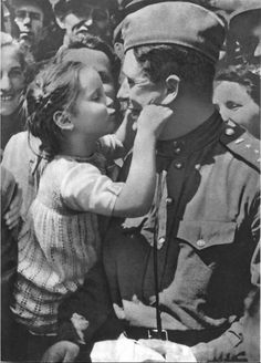 A little Czech girl from Praha plays with the captain of a tank unit after the liberation of the city.WWII