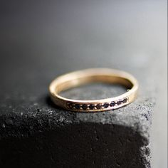 Black diamonds bring the drama to a simple gold band.