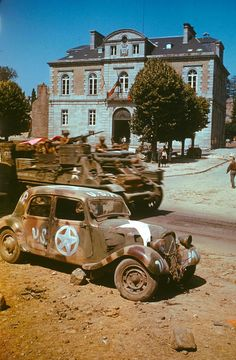 Armored vehicles on the move past civic buildings, and an abandoned car, in Avranches, France, summer D Day Normandy, Normandy France, Self Propelled Artillery, D Day Invasion, Jeep, Citroen Traction, Traction Avant, D Day Landings, Panzer