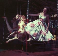 A woman riding the merry-go-round at Battersea funfair, wearing a floral print sun dress, 1955.