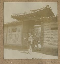 "[Soldiers guarding gate] Date: ca.1904 / Two Japanese soldiers stand guard (somewhat leisurely) in front of a modern brick compound. The signboard on the right side of the wall reads in translation: ""[Japanese] Army Headquarters stationed in Korea"" written in Chinese characters. Collection: Willard Dickerman Straight and Early U.S.-Korea Diplomatic Relations, Cornell University Library"