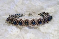 Sterling silver filled wire woven bracelet with scalloped edge and blue iridescent glass seed beads. Bracelet measures 1/2 wide. The wire is aged and buffed for a rich look. Fits average size wrist. Easy to fasten hook and loop closure. This is a Lisa Barth inspired design.