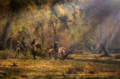 """""""INTO THE LIGHT"""" by PRISCILLA BURGERS """"Into the Light"""" is a photograph of four cowboys and their horses pausing on their ride in a central Arizona ranch to enjoy the sun's rays."""