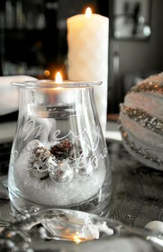 Use fat low empty candle jars with candle inside on fake snow .   Add small silver balls