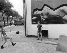 Robert Doisneau. Enfants // Garçons ballon devant affiche sous vetements