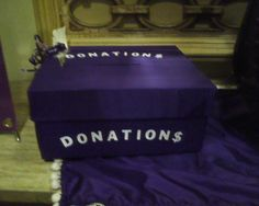 Donations box (covered in purple fabric) for class reunion. Used spray adhesive. Spray on box with lid. Can do w/o lid, and bottom trap door. Cover with fabric. Cut and tuck under. White sticky letters, and a ribbon decoration that goes around box to keep closed. 2010