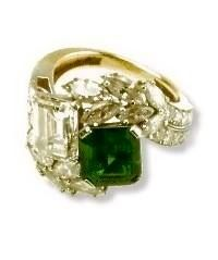 The engagement ring John F. Kennedy presented to Jacqueline Bouvier consisted of one 2.88 carat diamond mounted next to a 2.84 carat emerald cut emerald with tapered baguettes. The cost was over $1.5 million dollars. In 1962, the ring was reset to include round diamonds totaling .66 carats and marquise diamonds totaling 1.46 carats. After JFK's death, Jackie decided to have her engagement ring reset in the original design JFK so carefully had chosen for her.